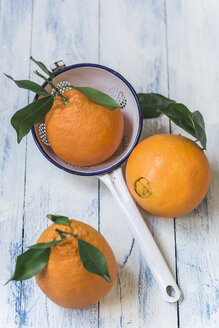 Three oranges with leaves and a colander on wood - STBF00281