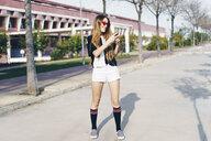 Spain, smiling teenage girl using smartphone on a road - ERRF00831