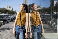 Spain, teenage girl with earphones leaning on a windowpane in sunshine - ERRF00858