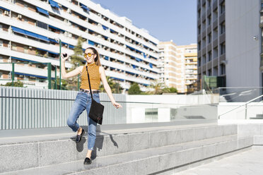 Spain, happy teenage girl dancing on stairs in the city - ERRF00861