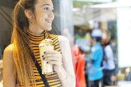 Spain, smiling teenage girl enjoying a milk shake - ERRF00870