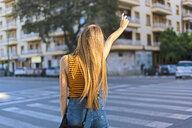 Spain, teenage girl hailing a taxi - ERRF00882