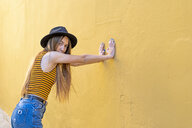 Portrait of teenage girl wearing hat at yellow wall - ERRF00885