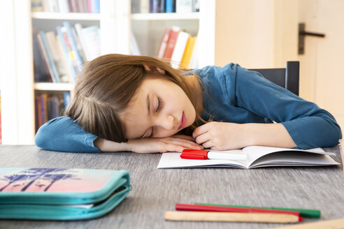 Schoolgirl napping at table with homework - LVF07943