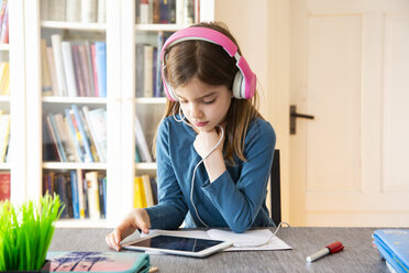 Little girl doing homework with headphones and digital tablet - LVF07946