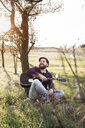 Man playing guitar at a tree on a meadow - HMEF00276