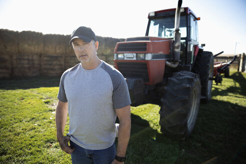 Portrait confident male farmer standing in front of tractor on sunny farm - HEROF33594