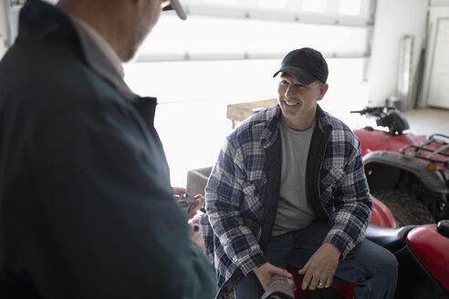 Male farmers talking in barn - HEROF33612