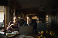 Couple paying bills at laptop in kitchen - HEROF33651