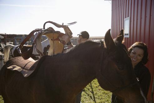 Ranchers saddling horse on farm - HEROF33693