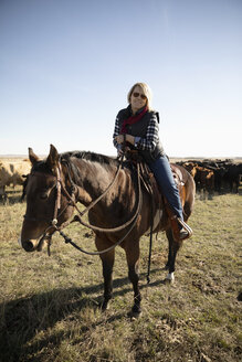 Female rancher on horseback in sunny field - HEROF33702