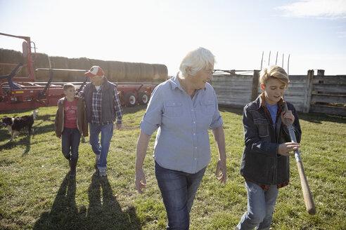 Senior couple farmers and grandsons working on sunny farm - HEROF33705