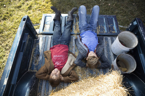 View from above carefree brothers relaxing, laying in pickup truck bed on farm - HEROF33714