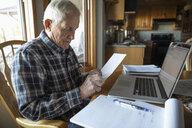 Senior man paying bills at laptop in kitchen - HEROF33723