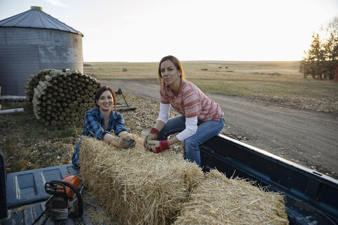 Portrait confident female farmers with hay bales on pickup truck on farm - HEROF33729