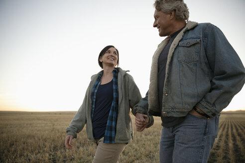 Farmer couple holding hands, walking in field - HEROF33735