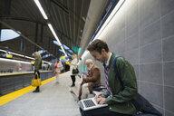 Businessman using laptop on bench subway station platform - HEROF33738