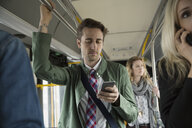 Businessman texting with cell phone standing on bus - HEROF33750