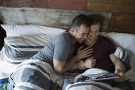 Affectionate homosexual couple using digital tablet in bed - HEROF33867