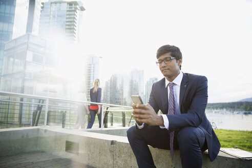 Businessman texting with cell phone at city waterfront - HEROF33909