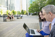 Businessman and businesswoman using laptop in city park - HEROF33927