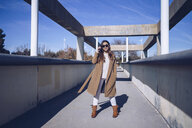 Young woman wearing coat and sunglasses standing on a bridge - RSGF00169