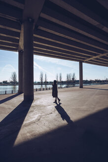 Young woman walking at an underpass at a lake - RSGF00172