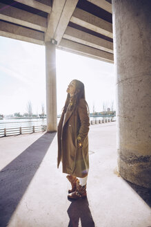 Young woman standing at an underpass at a lake with closed eyes - RSGF00175