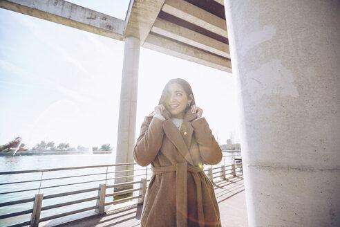 Smiling young woman at a lake - RSGF00178