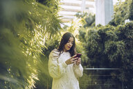 Young woman using cell phone in a park - RSGF00184