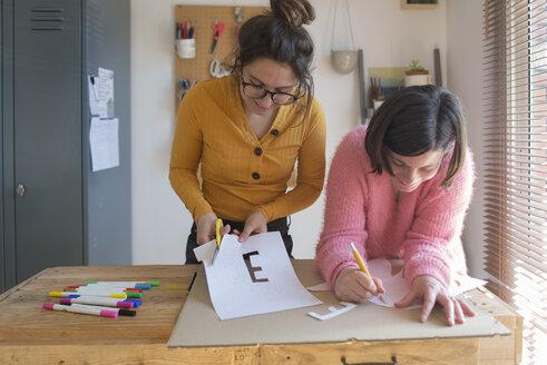 Two women making stencils for printing sweatshirts - SKCF00577