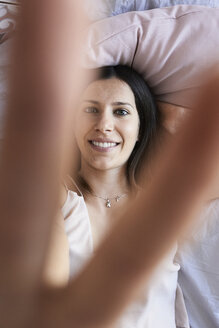 Portrait of smiling young woman lying on bed showing victory-sign, top view - IGGF00936