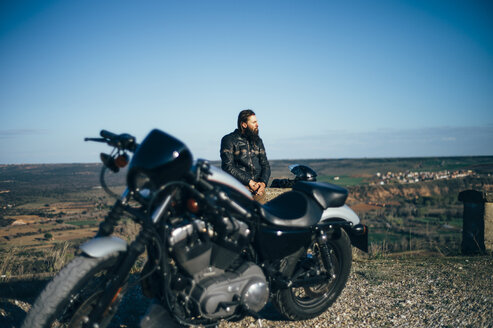 Man with custum motorcycle having a break at sunset - OCMF00343