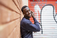 Portrait of happy young man listening music with wireless earphones and smartphone - OCMF00349