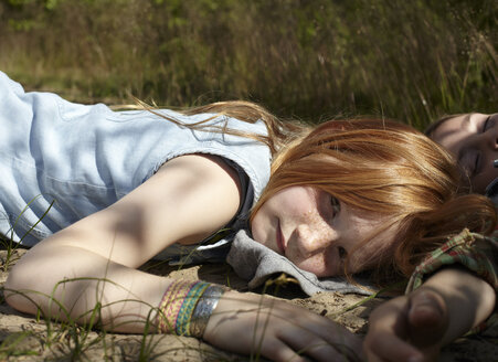 Portrait of redheaded girl lying on sandy soil - AMEF00059