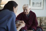 Home caregiver explaining prescription pill box to senior man - HEROF33960