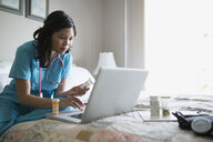 Home caregiver with prescriptions using laptop on bed - HEROF34005