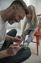 Father painting daughters toenails with nail polish - HEROF34038