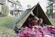 Father and son using digital tablet in backyard tent - HEROF34068