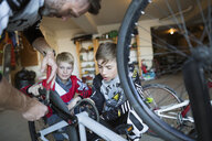 Father teaching sons how to repair bicycle in garage - HEROF34071