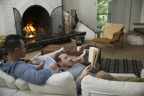 Homosexual couple relaxing reading book and digital tablet near fireplace in living room - HEROF34149