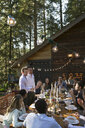 Homosexual couple addressing friends at long table at wedding reception - HEROF34161