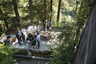 Friends talking around long dining table on balcony in woods at wedding reception - HEROF34173