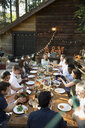 Friends dining around long dining table on balcony at wedding reception - HEROF34179