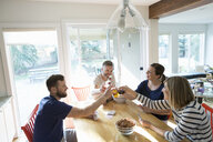 Couples toasting beer and playing cards at dining table - HEROF34203
