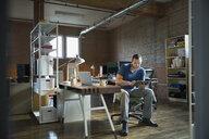 Creative businessman using digital tablet at desk - HEROF34215
