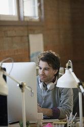 Designer with headphones working at computer in office - HEROF34227