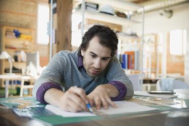 Designer using ruler and bradawl blade on cutting mat in office - HEROF34230