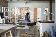 Creative businesswoman using laptop cross-legged in office - HEROF34233
