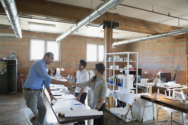 Designers handshaking over plans in office - HEROF34245
